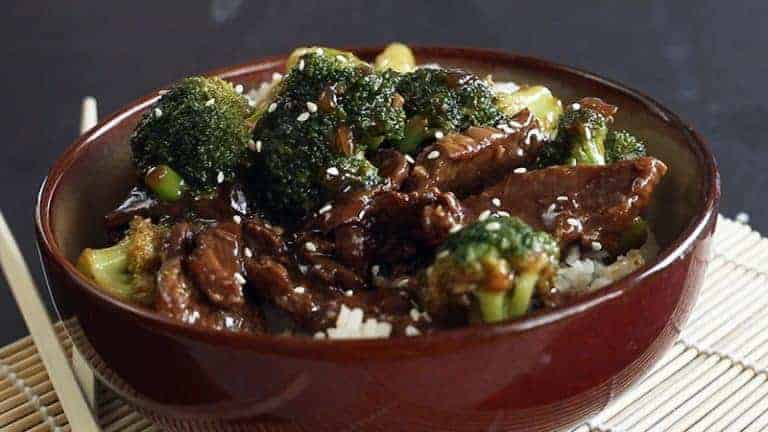 a bowl of beef and broccoli over rice