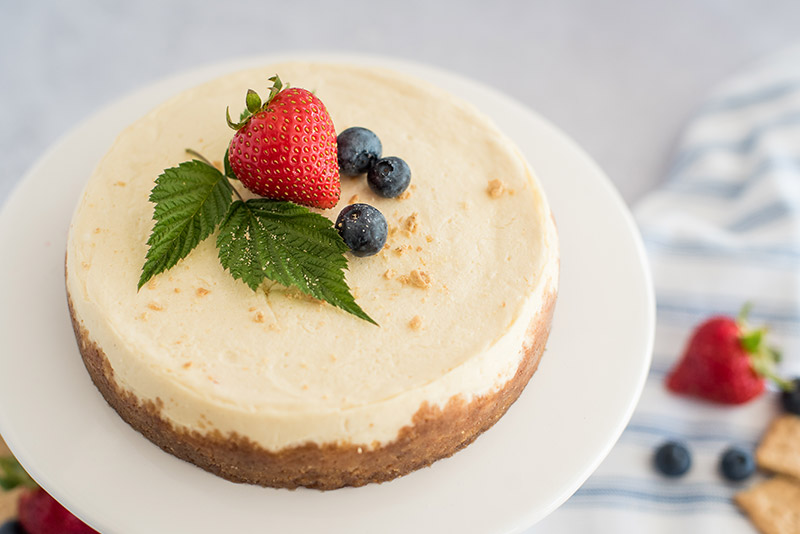 This easy Instant Pot cheesecake is garnished with simple mint leaves and berries.