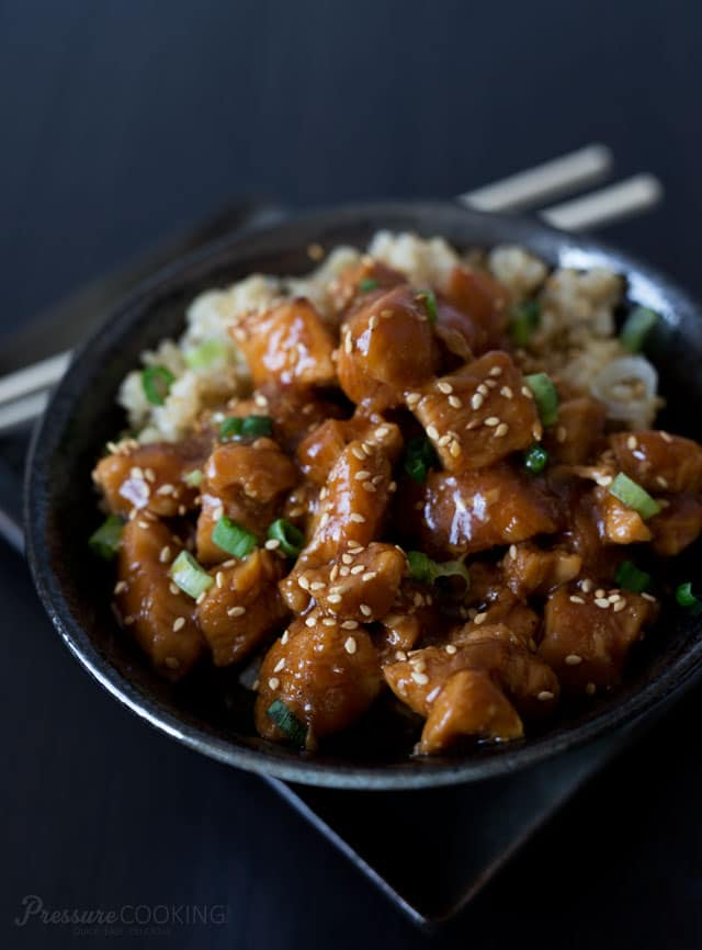 honey sesame chicken in a black bowl over rice