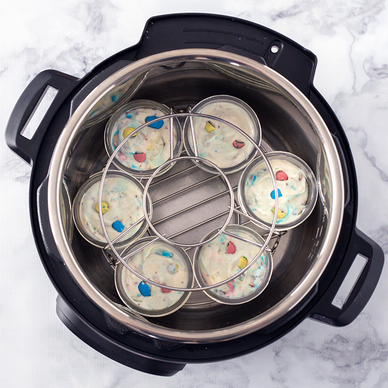 Six Instant Pot mini cheesecakes in the bottom of the pressure cooking pot, with a second trivet stacked on top