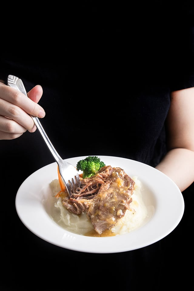 someone holding a white dinner plate with shredded Asian pork. A fork is in the right hand.