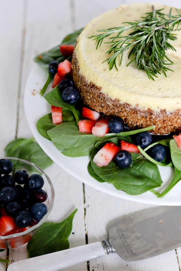 Pressure Cooker Savory Blue Cheese Cheesecake garnished with fresh rosemary, surrounded by a strawberry spinach salad,
