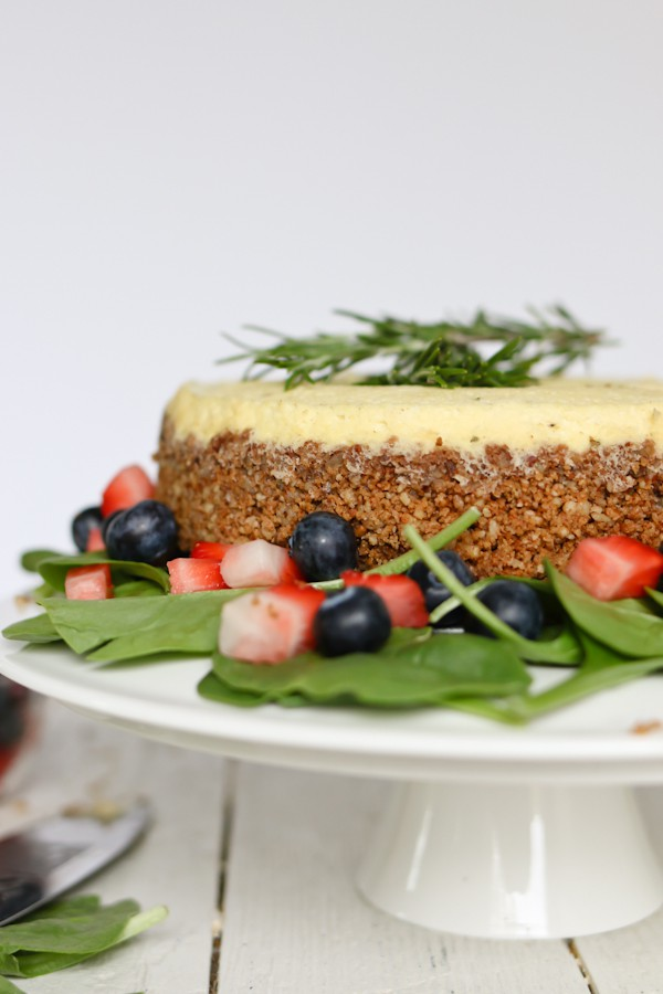 cake plate holding a savory cheesecake made with blue cheese, surrounded by a spinach salad with blueberries and strawberries