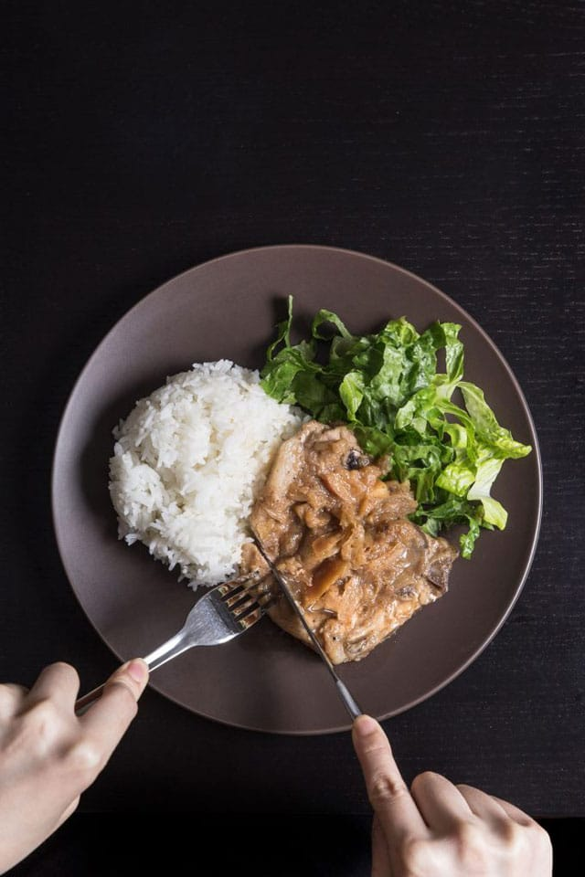 brown dinner plate with pork chops made in a pressure cooker, along with white rice and a green salad