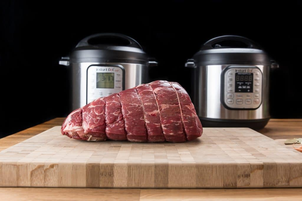 uncooked beef roast on a cutting board with two electric pressure cookers behind it