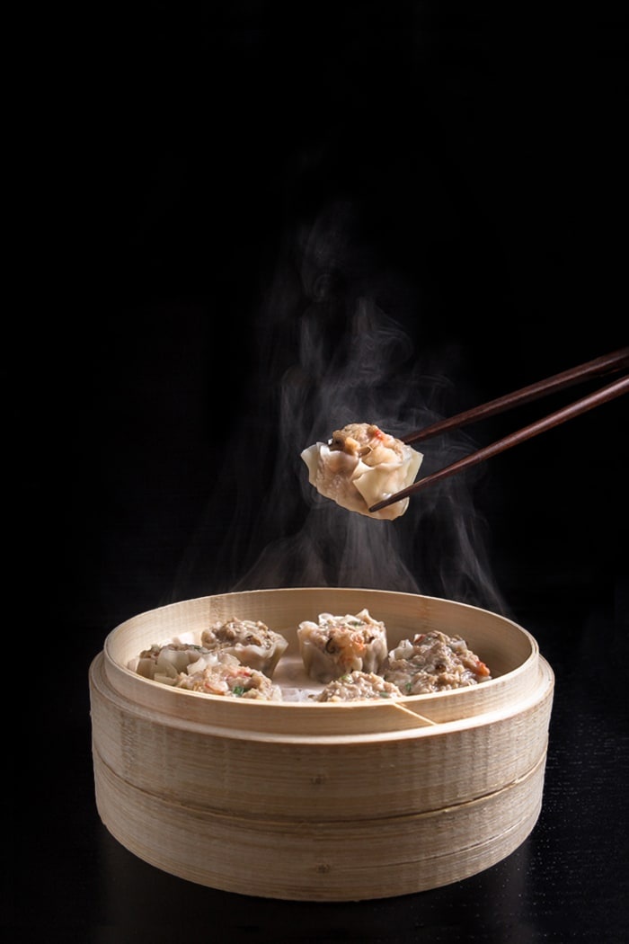 Shumai (Shrimp & Pork Dumplings) in a steamer basket. One dumpling being held with chopsticks