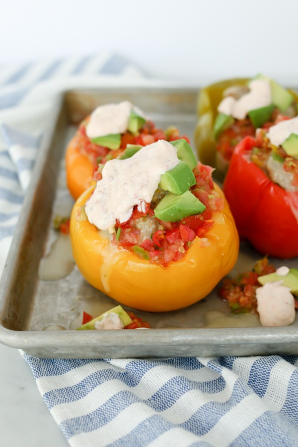 a rimmed baking sheet with Mexican stuffed peppers topped with chipotle lime sauce
