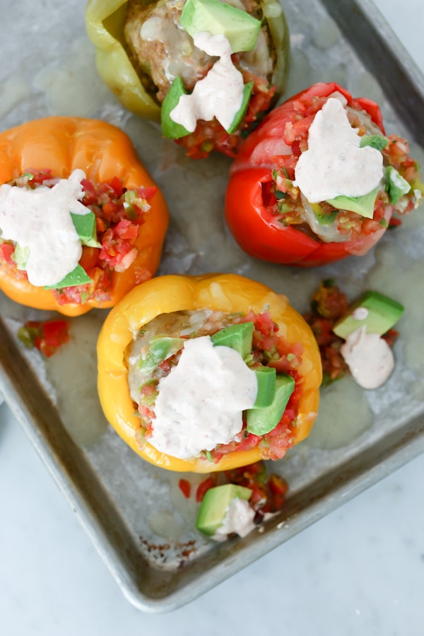 overhead image of 4 bell peppers stuffed with Mexican spiced ground turkey filling