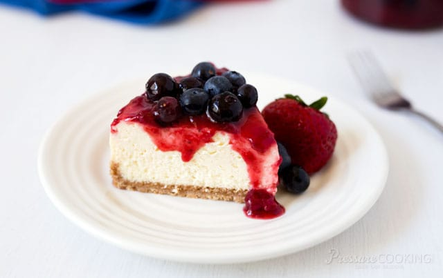 slice of red white and blue cheesecake on a white dessert plate. Creamy vanilla cheesecake topped with strawberry sauce and fresh blueberries
