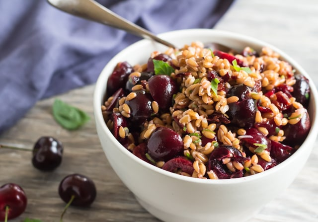 a white serving bowl and serving spoon in the bowl filled with a salad made with cherries and pressure cooker farro