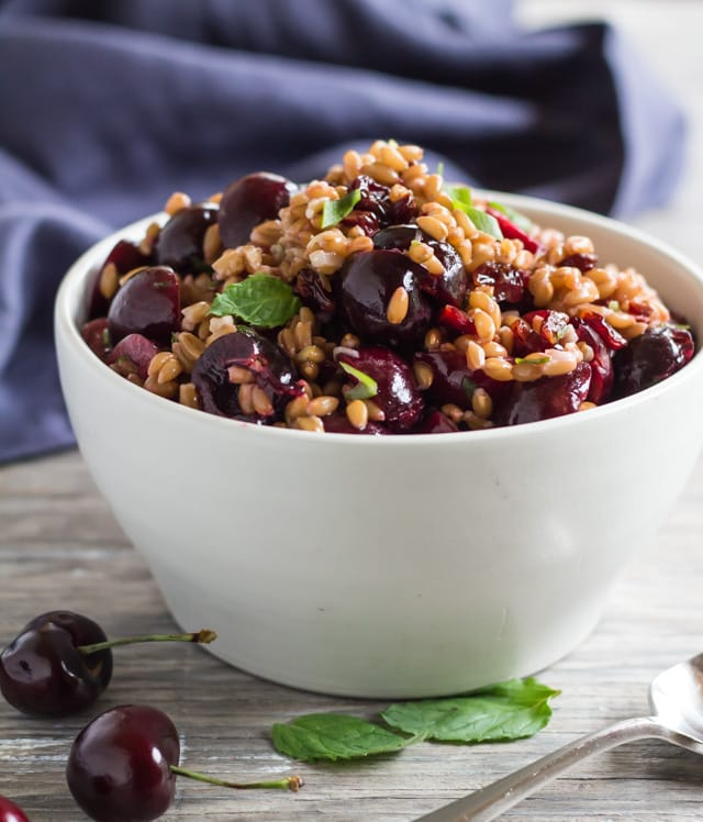 white serving bowl with Pressure Cooked Farro Salad with fresh cherries