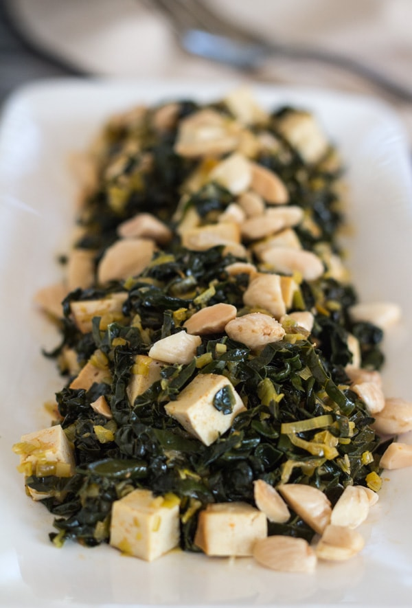 Pressure Cooker Kale with Baked Tofu and toasted almonds on a white serving platter
