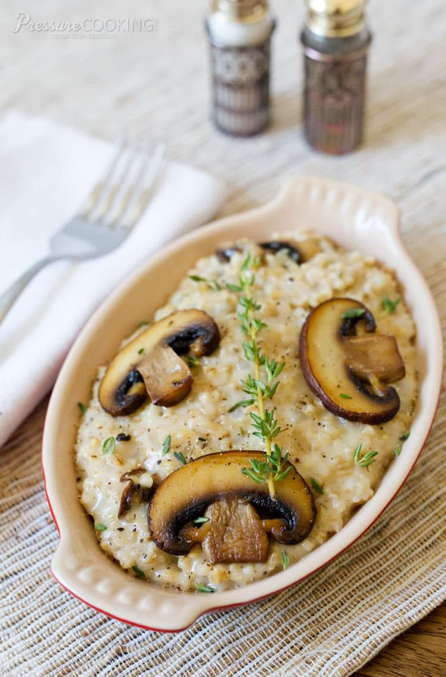 dish of savory mushroom thyme oatmeal garnished with sliced mushrooms and fresh thyme