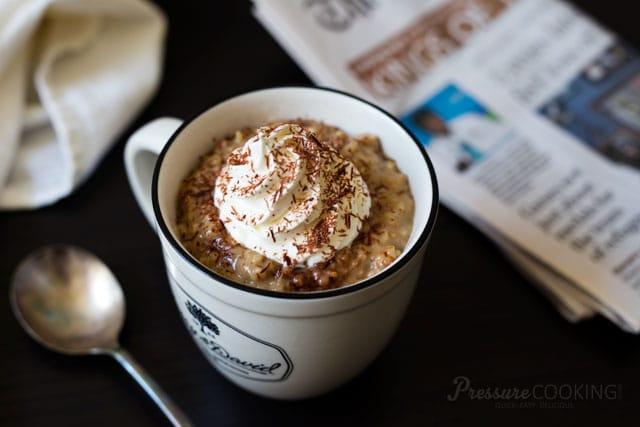 A coffee mug full of Pressure Cooker Vanilla Latte Steel Cut Oats topped with fresh whipped cream and shaved chocolate