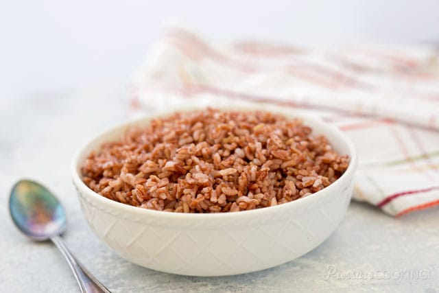 white bowl full of pink rice, made in an electric pressure cooker