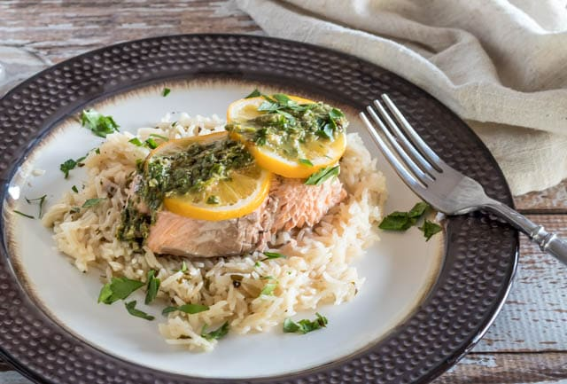 Salmon and Rice With Lemon Caper Chimichurri on a black and white dinner plate