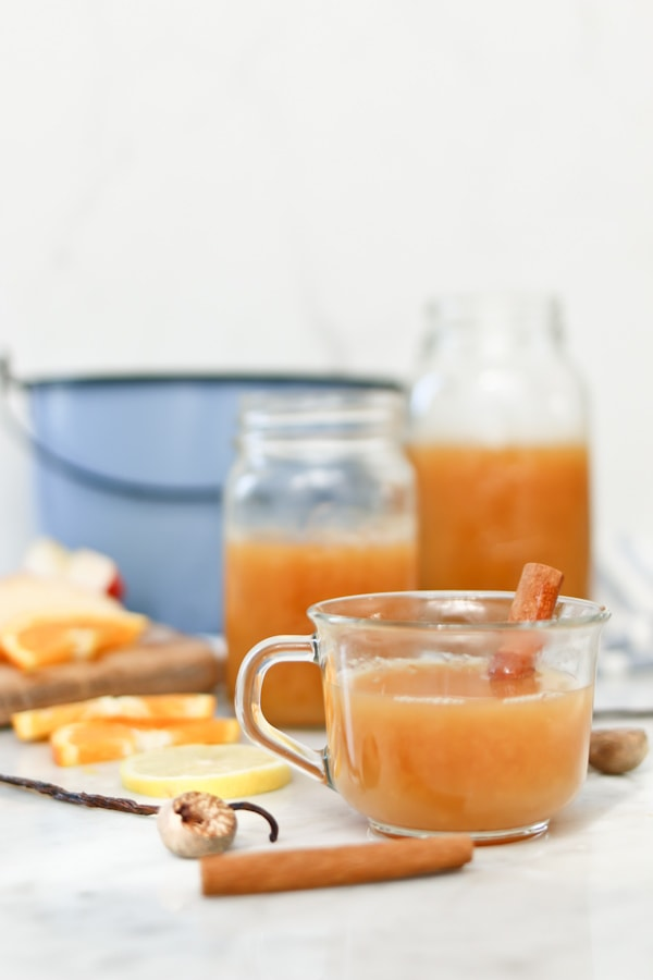 a batch of wassail made in an electric pressure cooker being served in clear coffee mugs with a cinnamon stick