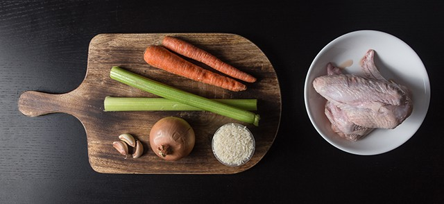 cutting board with 2 unpeeled carrots, 2 stalks of celery, 3 cloves of garlic, 1 onion, and a cup of uncooked rice. Next to it is a bowl of raw chicken.