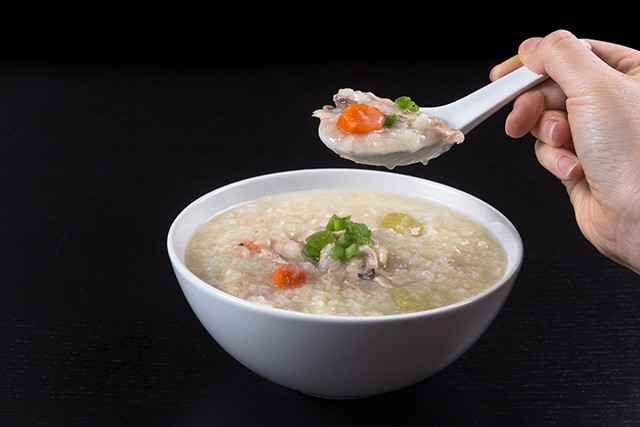 white bowl of Pressure Cooker Turkey Rice Porridge with white soup spoon full of the porridge above the bowl.