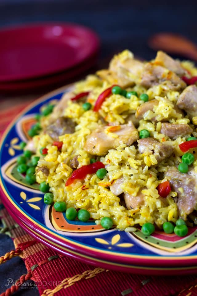 This Pressure Cooker Arroz con Pollo is a saffron braised chicken and rice dish served family style on a large platter garnished with pimiento and peas.