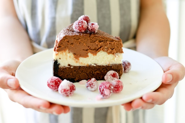 white plate with a large slice of Triple Chocolate Layered Cheesecake garnished with sugared cranberries