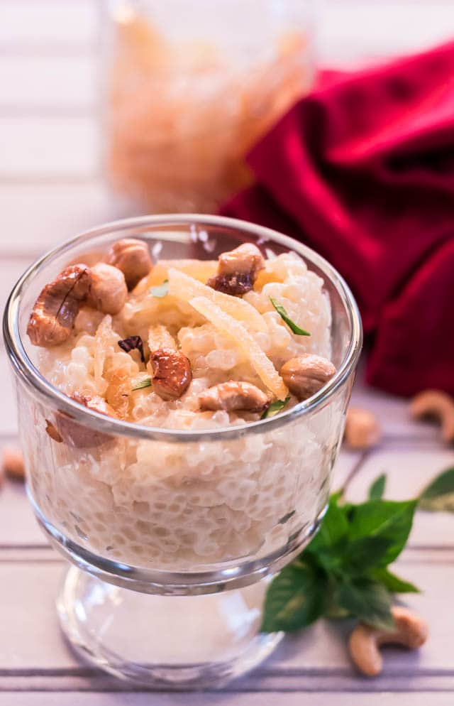 clear dessert cup with Pressure Cooker Coconut Lemongrass Ginger Tapioca garnished with cashews and crystallized ginger