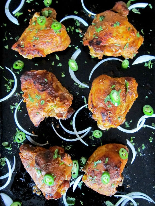 6 pieces of Pressure Cooker Tandoori Chicken garnished with raw onion and sliced jalapenos