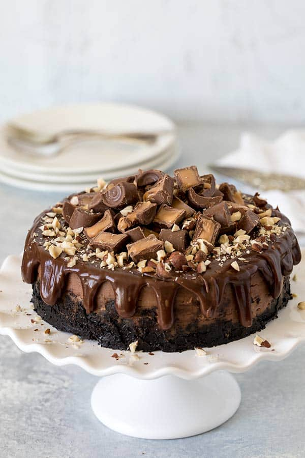 A rich, creamy, decadent Nutella cheesecake topped with chocolate ganache, Rolo Candies, and chopped hazelnuts.