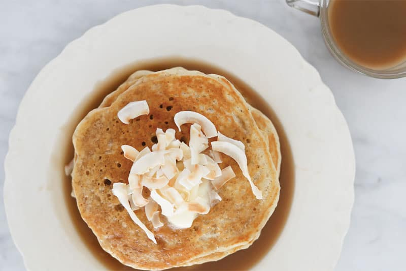 Plate of pancakes topped with Coconut Vanilla Syrup made in a pressure cooker
