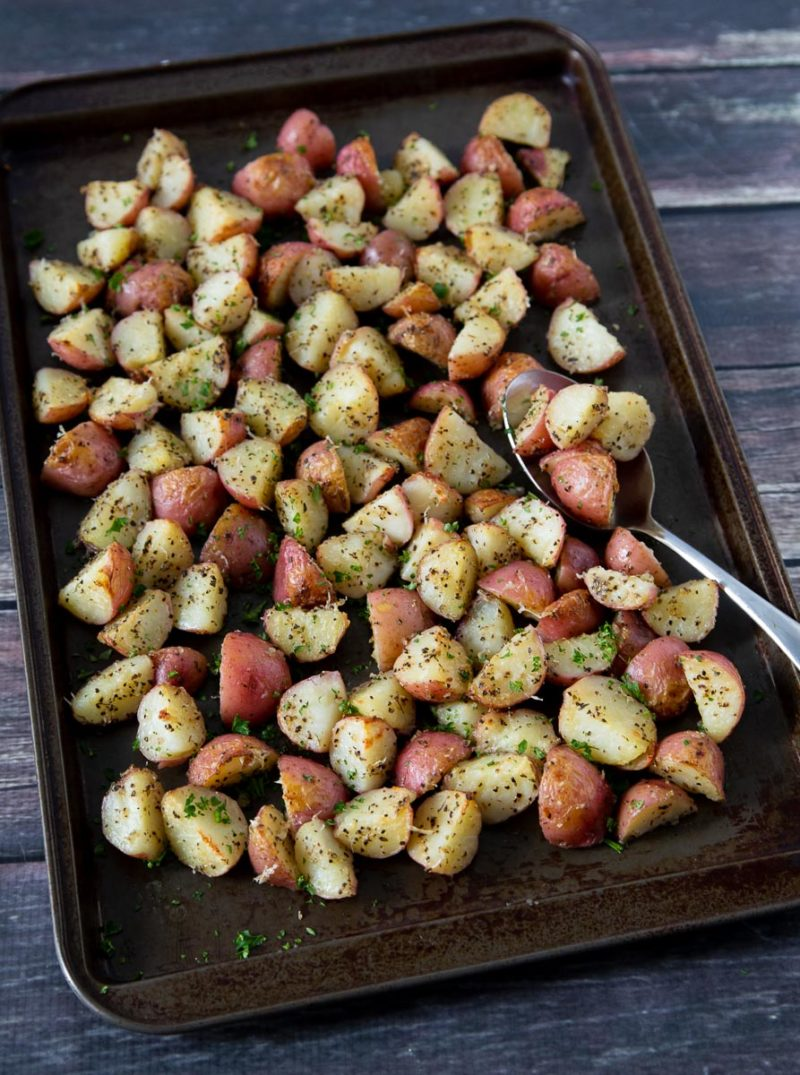 A sheet pan full of prepared Instant Pot / Pressure Cooker Garlic Herb Roasted Red Potatoes
