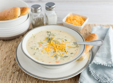 Pressure Cooker Broccoli Cheese Soup, dished up and ready to serve with additional shredded cheese and breadsticks