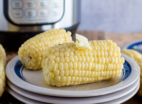 Easy Pressure Cooker Corn on the Cob, plated with an Instant Pot in the background