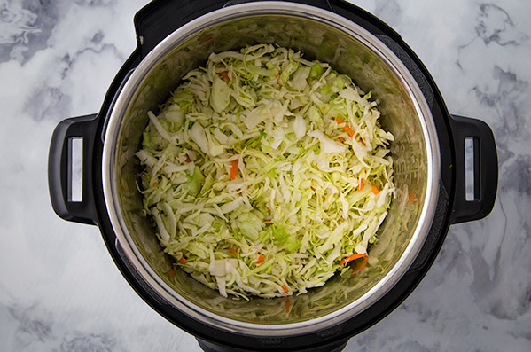 pressure cooking egg roll with cabbage on top in an Instant Pot