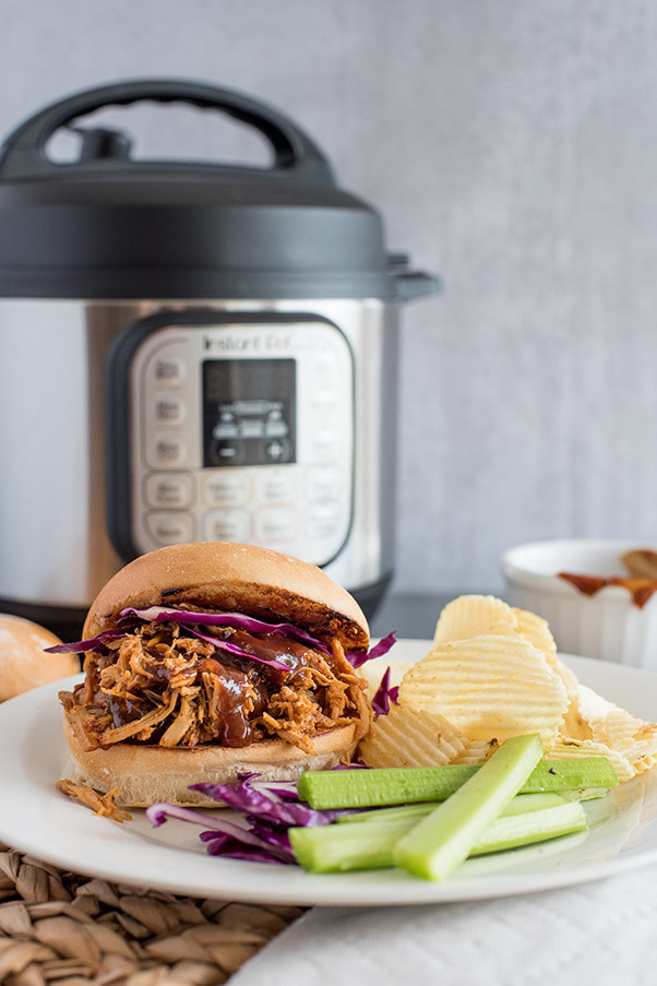 plated Instant Pot Pulled Pork sandwich, with an Instant Pot in the background.