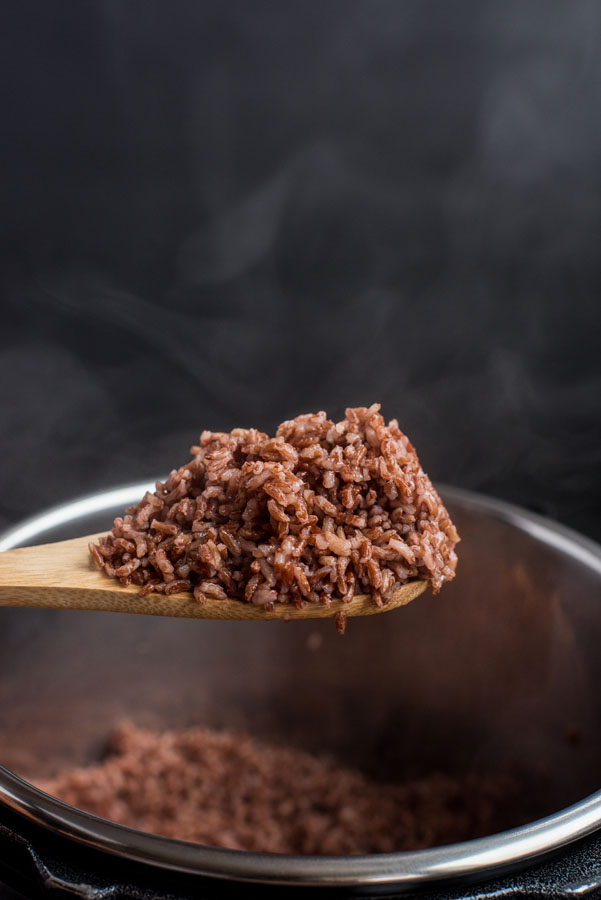 A spoonful of prepared Instant Pot pink rice, with steam rising from the spoon.