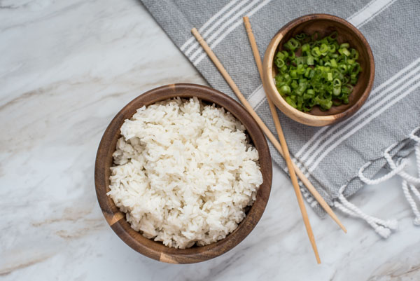 An overhead shot of white rice prepared in the Instant Pot and green onions, with chopsticks balanced between the bowls