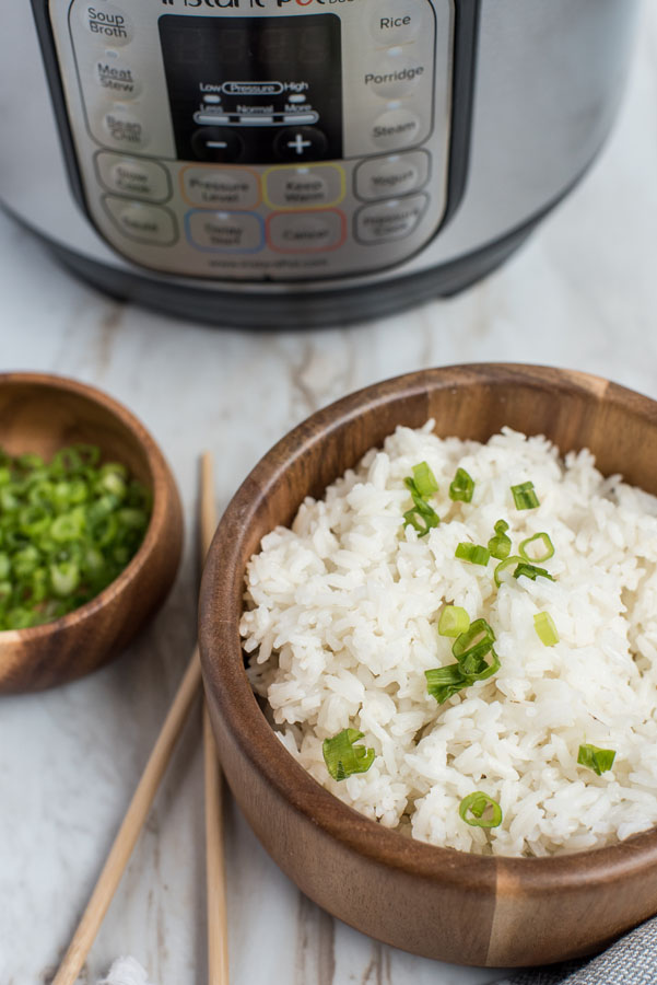 Pressure Cooker White Rice prepared with a green onion garnish and an Instant Pot in the background