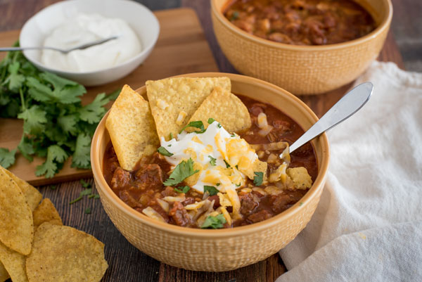 Beef and Bean Instant Pot Chili, dished up in a yellow serving bowl, topped with tortilla chips, sour cream, cheddar cheese, and cilantro