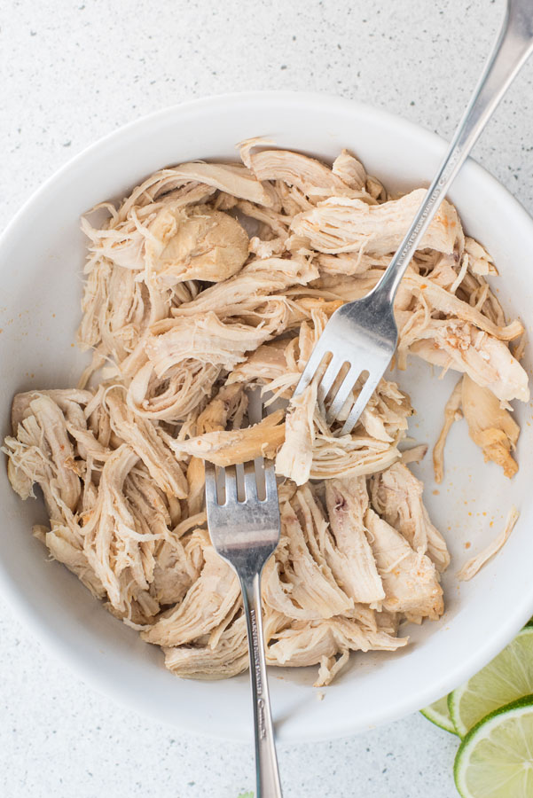 A bowl of pressure cooker chicken taco filling being shredded with two forks.