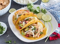 A plate of three Instant Pot chicken tacos, filled with rice, cilantro, avocado, and diced tomato, garnished with two lime slices and a spring of cilantro