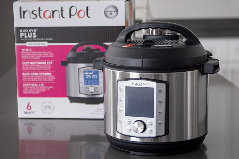 Instant Pot Duo Evo Plus sitting on a gray countertop with the InstaPot Evo packaging in the background.