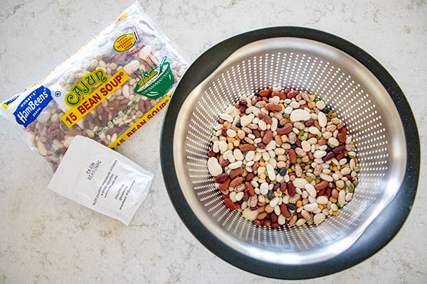 A 20 ounce package of HamBeens Cajun 15 Bean Soup and beans in a colander.