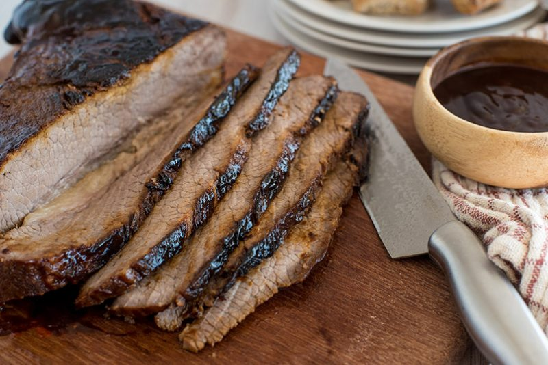 Instant Pot brisket sliced on a cutting board with bbq sauce.