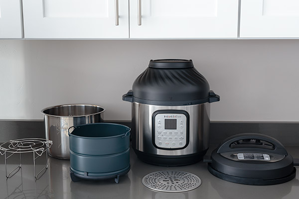 Instant Pot Duo Crisp with air fryer lid and accessories that include, trivet and dual layer air fryer basket.
