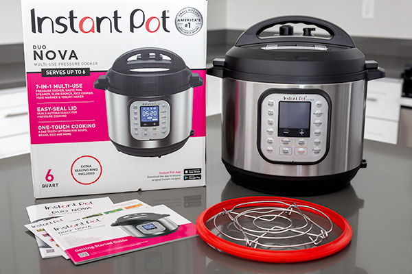 Instant Pot Duo Nova shown with provided accessories including extra sealing ring, trivet that can fold flat, getting started guide, and cooking times diagram.