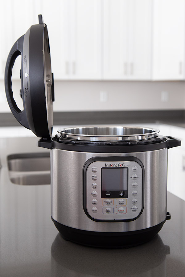 Instant Pot Duo Nova with the pressure cooker lid placed on the side holder.