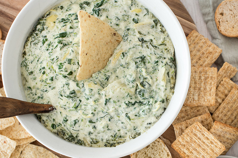 Hot spinach artichoke dip served with crackers and bread.