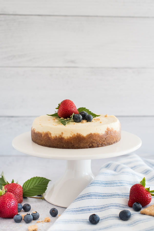 Profile view of an Instant Pot cheesecake on a cake stand, topped with berries.
