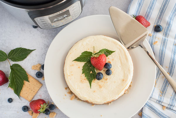 A top view of Instapot cheesecake, garnished with a strawberry and blueberries and mint leaves, with a silver server and an Instant Pot in the background