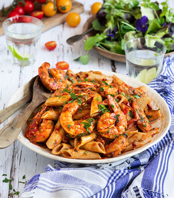 45 degree of Instant Pot Shrimp Fra Diavlo over Penne Pasta in a white bowl with wooden serving spoons and a blue and white checkered cloth.